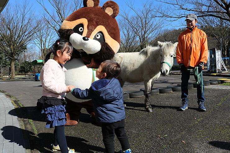 パークのキャラクター「里ノ助」と野間馬の出迎えに笑顔の子どもたち