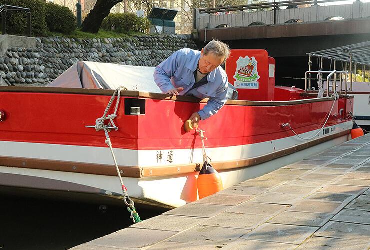 遊覧船の船体をスポンジで磨く参加者