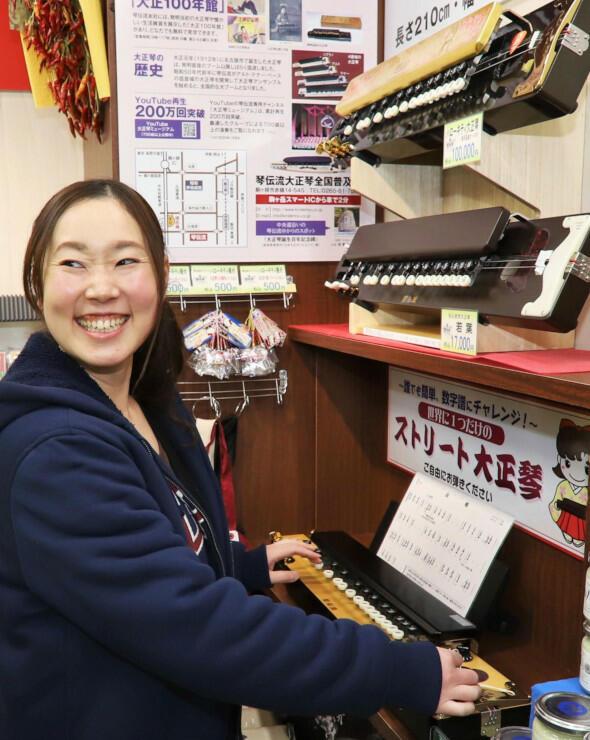 駒ケ岳SA売店の一角に設置された「ストリート大正琴」を弾く人