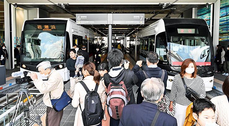 岩瀬浜行き(左)と環状線の路面電車が並ぶホーム。南北直通運転初日は大勢の人でごった返した=21日午前11時半ごろ、富山駅北口