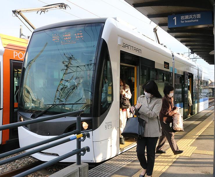 岩瀬浜行きの車両「サントラム」から降車する利用客=23日、城川原駅