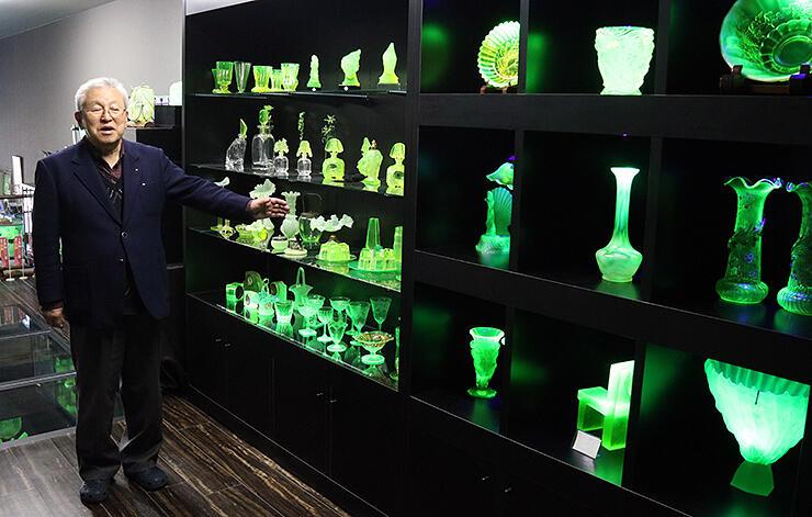 黄緑色に光るウランガラス作品が並ぶ館内。左は新森さん
