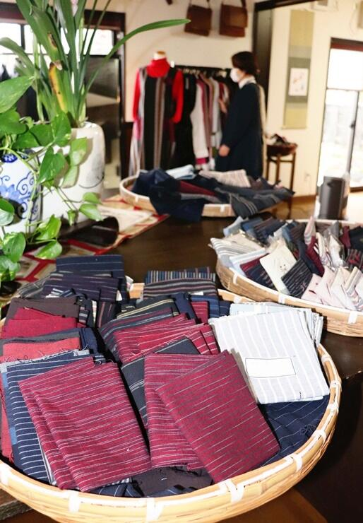 亀田縞の小物や服などがずらりと並び、にぎやかな雰囲気を演出している展示販売会=聖籠町
