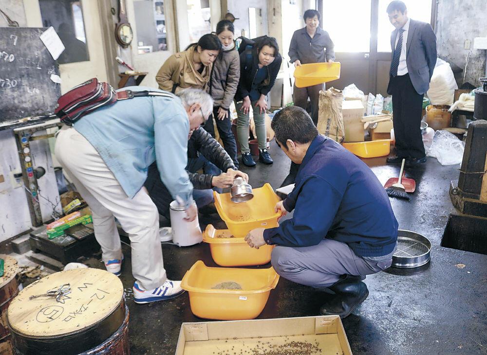 ウルシの種ろうを取り除く作業に取り組む参加者=輪島市釜屋谷町