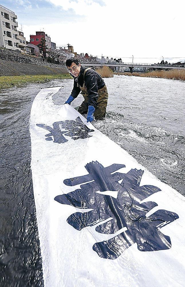 のぼり旗ののりを落とす平木さん=新橋周辺の犀川