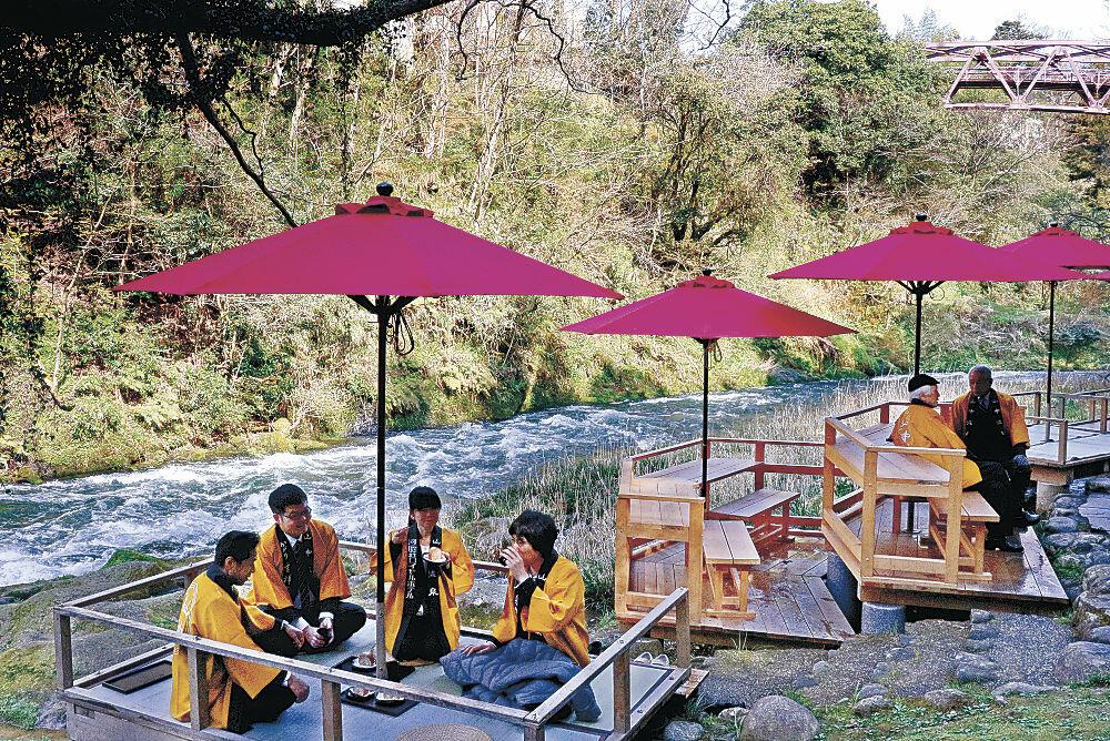 川床で景色を楽しみながら菓子を味わう来場者=加賀市山中温泉の鶴仙渓