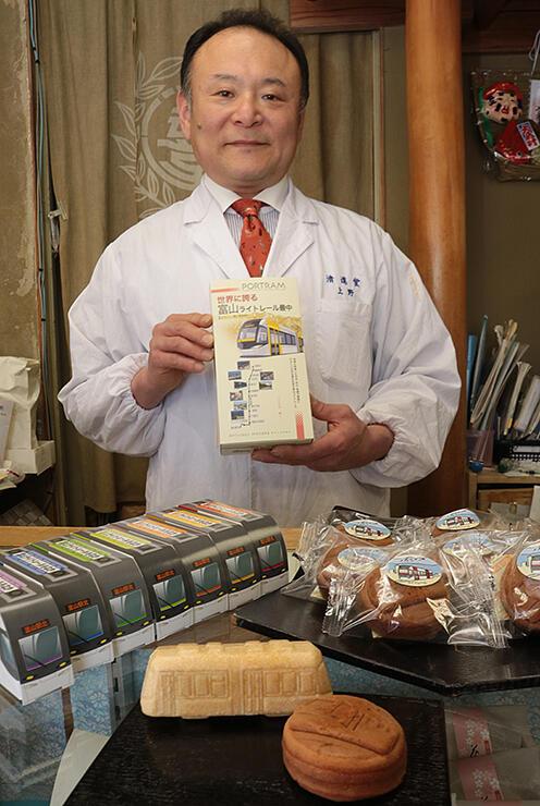 富山ライトレールをデザインしたもなかとまんじゅうを紹介する上野社長