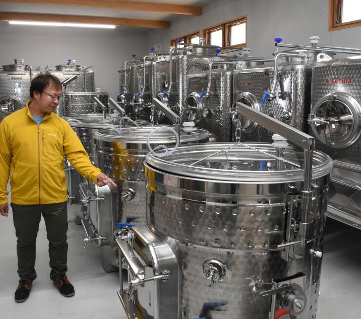 醸造タンクについて説明する横山社長