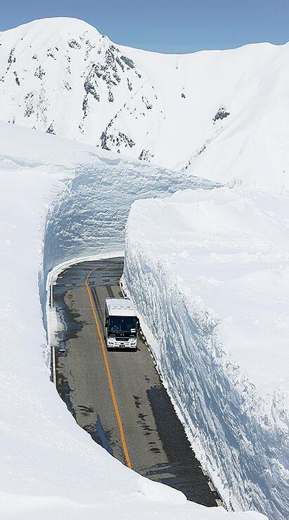 高さ15メートルの雪壁がそびえる雪の大谷を走る高原バス=立山・室堂付近