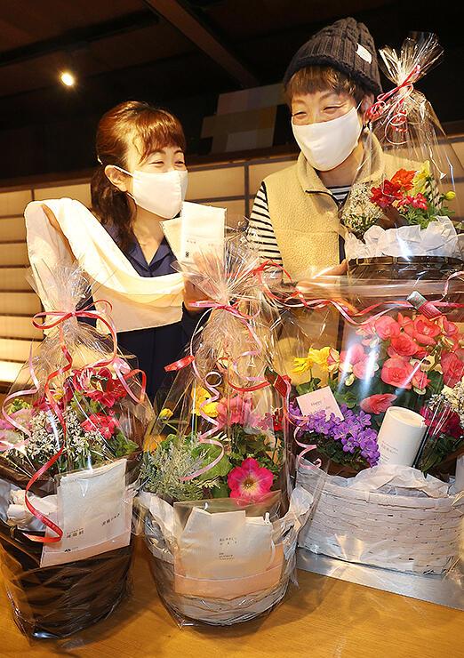 「母の日」に向けて企画したコラボギフトを前に、城端絹のマスクを着けて打ち合わせる松井さん(左)と石村さん