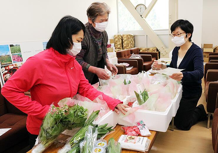 山菜の詰め合わせをを箱詰めする地元住民