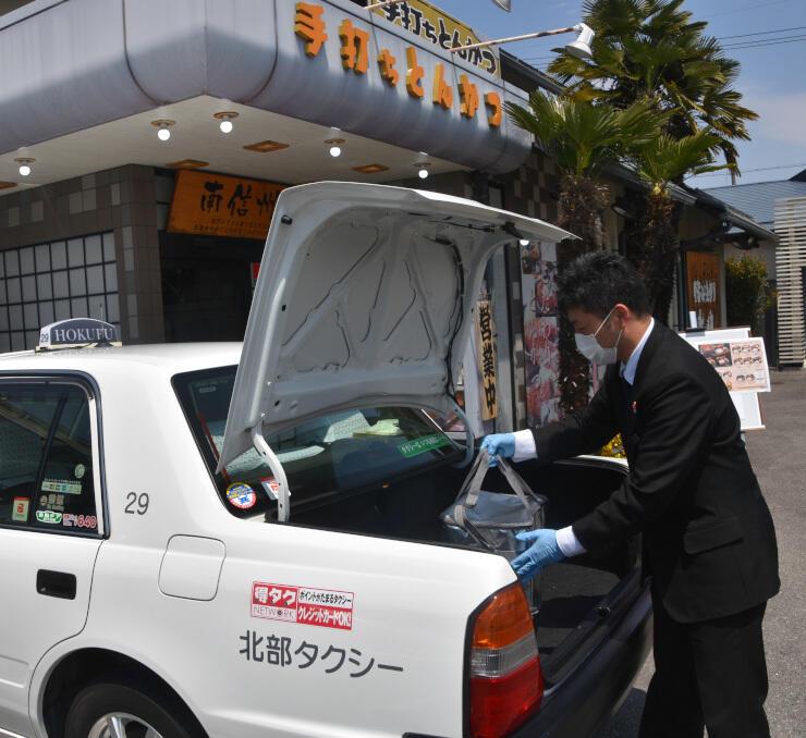 飯田市内のとんかつ店の弁当をトランクに入れる北部タクシーの運転手=27日