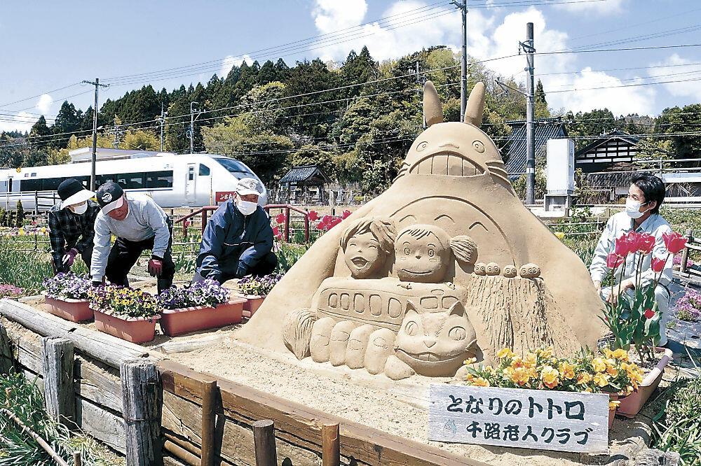 完成した砂像を見る古永さん(右)と西山さん(同2人目)ら会員=羽咋市千路町
