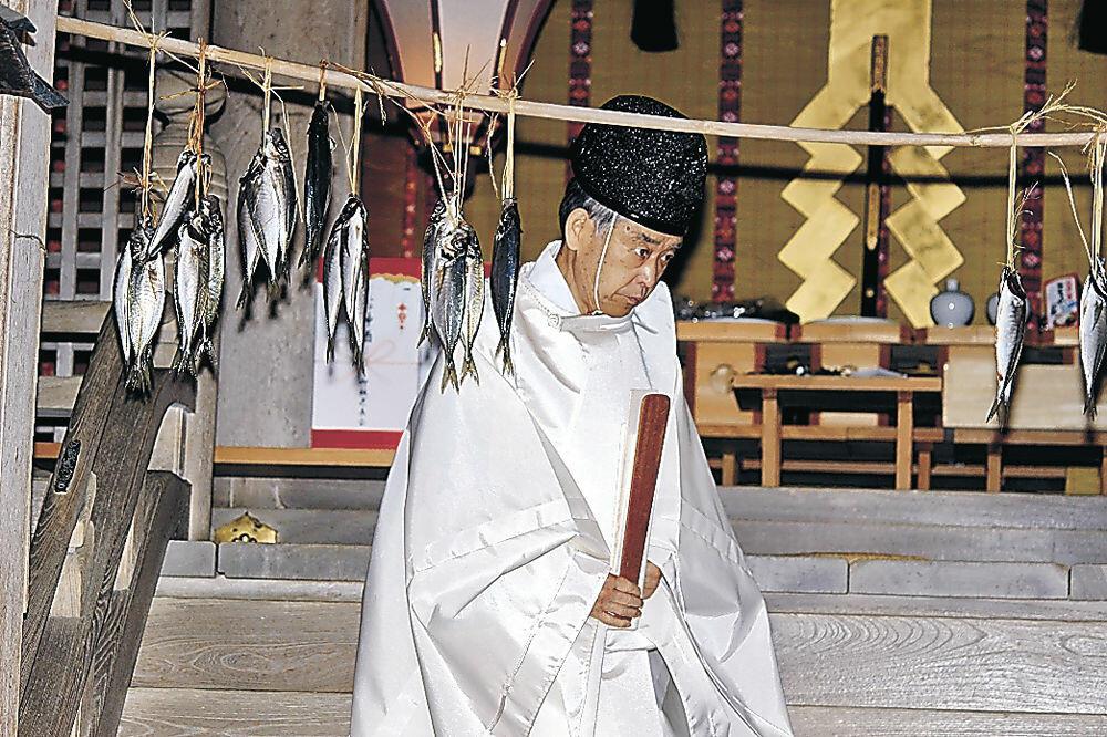 神前にアジがつるされた本殿で神事に臨んだ松尾名誉宮司=羽咋市の気多大社