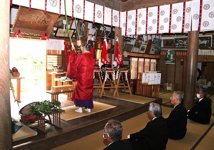 弓の弦を手で引き鳴らす「鳴弦」をして邪気をはらう野上宮司=加茂神社