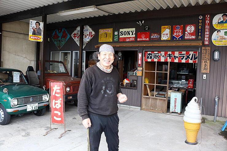 ホーロー看板や懐かしい車が並ぶ氷見昭和館別館の前で「新型コロナが終息したら来て」と笑顔を見せる蔵田館長