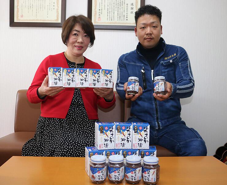 商品を手に笑顔を見せる川村社長(左)と悠樹専務