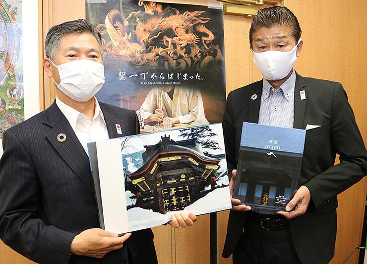 写真集を披露する三谷会長(左)と原田事務局長