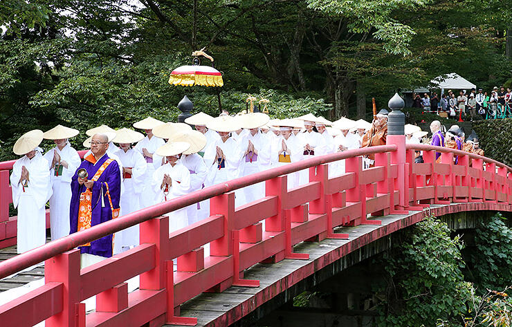 白装束に目隠しをして布橋を渡る女人衆 =2017年9月24日、立山町芦峅寺