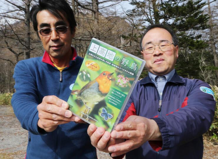 上高地の野鳥を紹介するDVDを手にする前田さん(右)と酒井さん