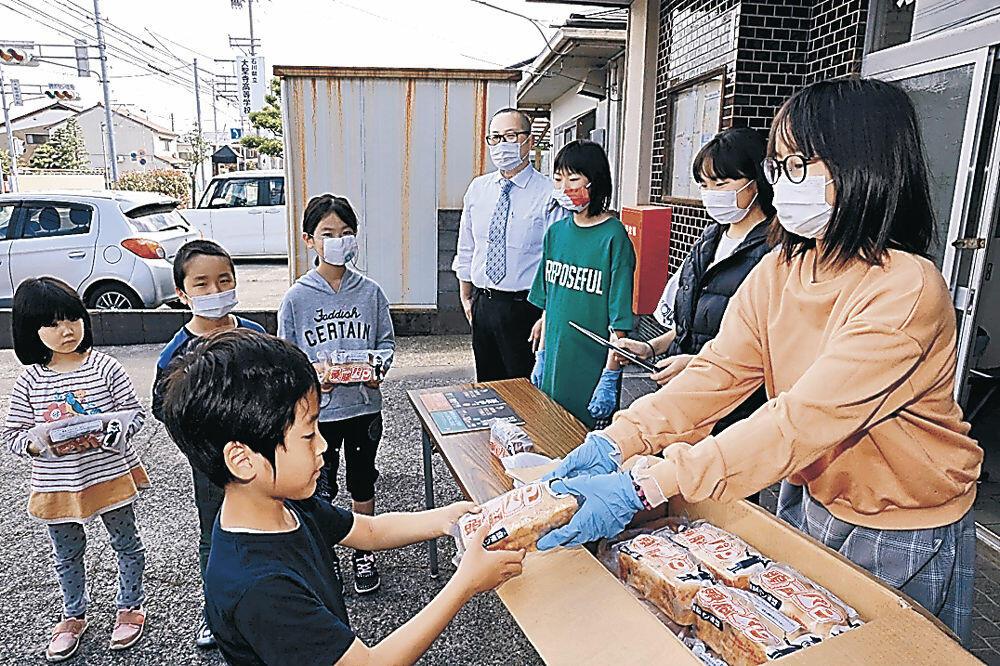 頭脳パンを受け取る児童=加賀市大聖寺永町