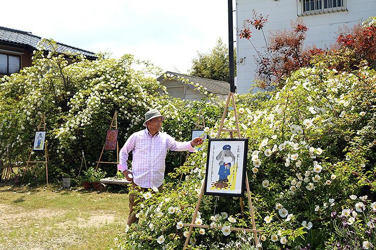 白バラの中に創作ポスターを展示した前庭