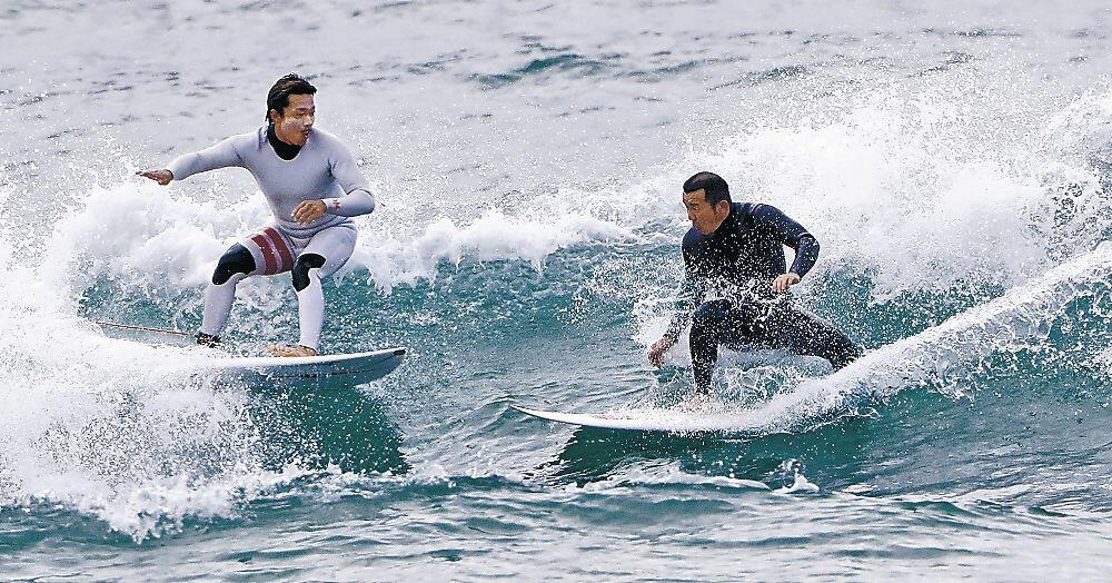 白いしぶきを上げながらサーフィンを楽しむ愛好者=内灘海岸
