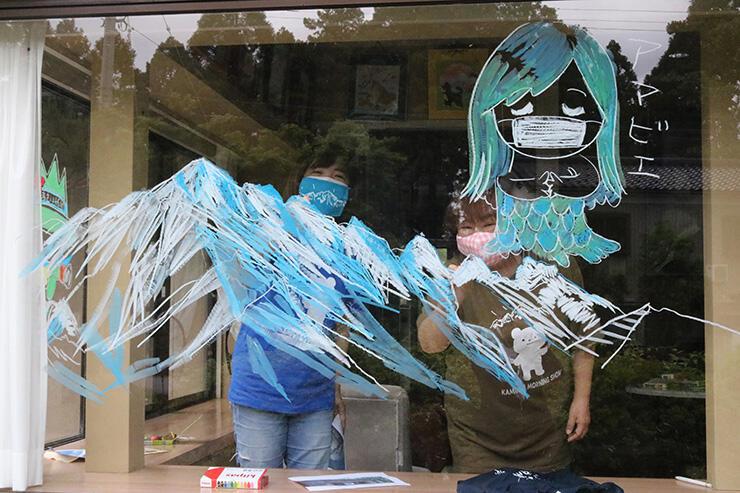 白萩西部公民館の職員(右)とイラストを描く金松さん=白萩西部公民館