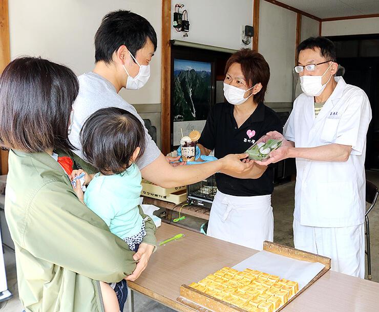 買い物客に商品を手渡す小蔵店主(右)と苗代代表(右から2人目)