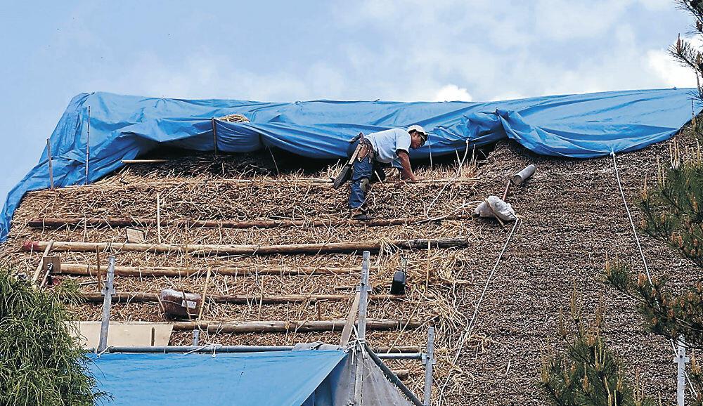 茅葺き屋根の葺き替え作業=輪島市三井町小泉