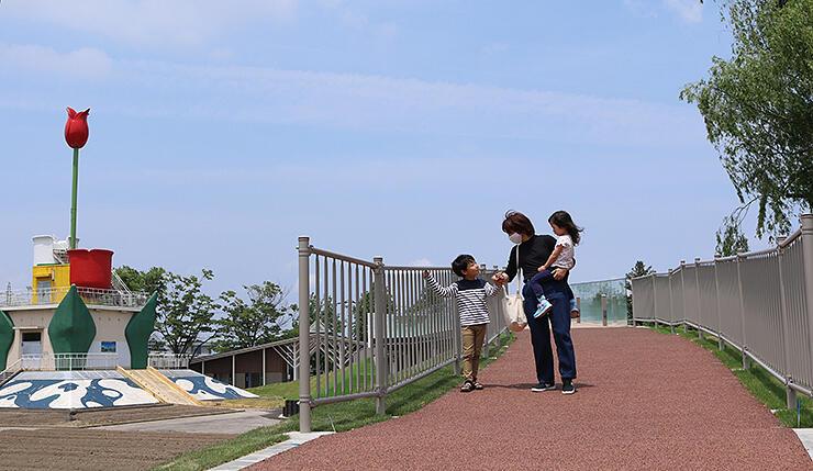 スカイウォークを渡る親子=砺波チューリップ公園