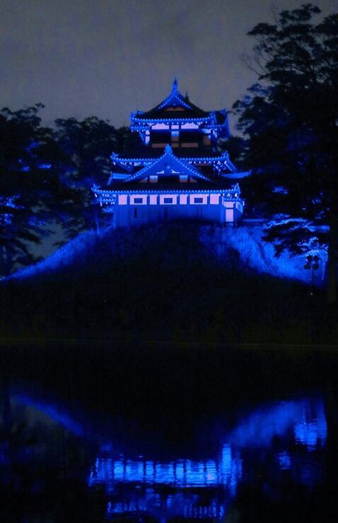 医療従事者らにエールを送るため、青い光で照らされた高田城址公園の三重櫓=27日、上越市