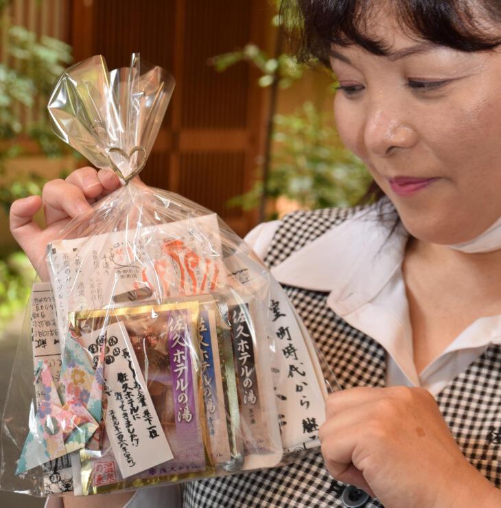 入浴剤と天茶が入った袋を手にする篠沢さん