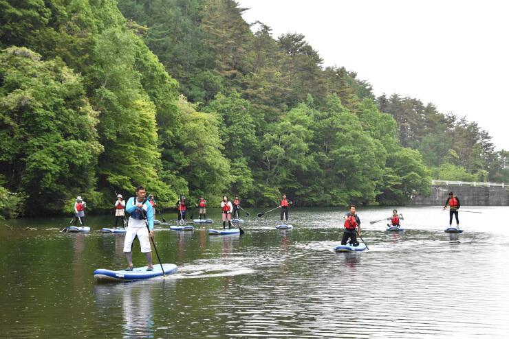 水上でボードの上に立ち、バランスを保ちながら進む参加者