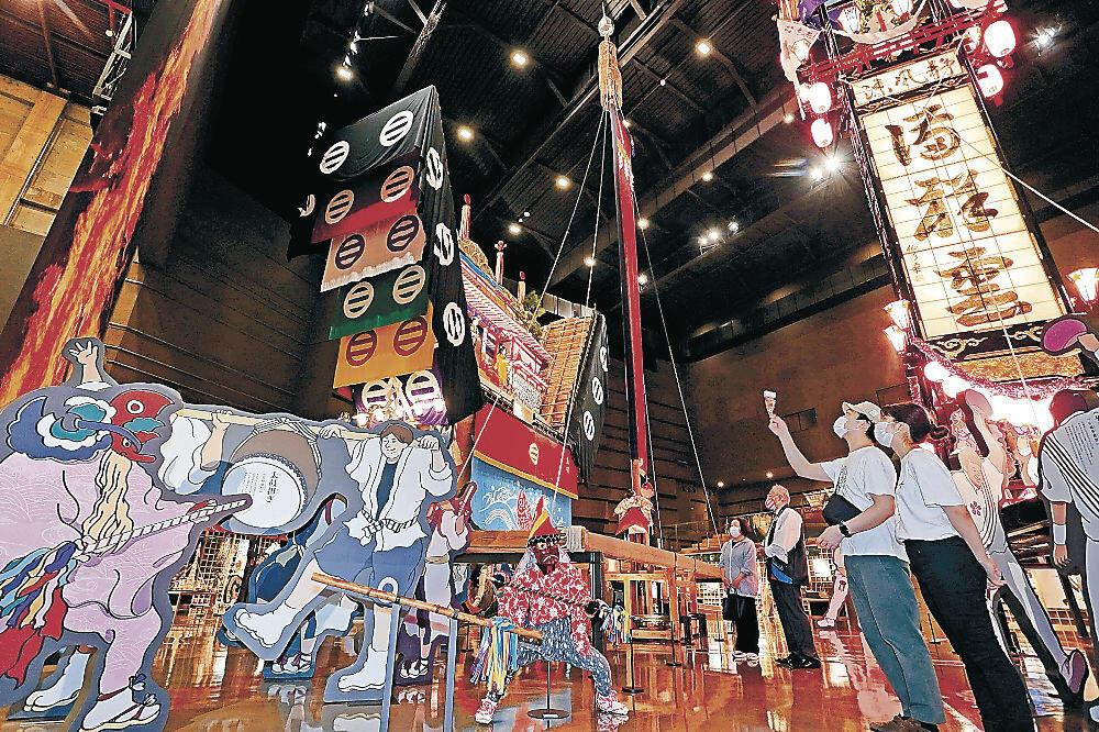 展示されたでか山や大奉燈などを見て回る来場者=七尾市の和倉温泉お祭り会館