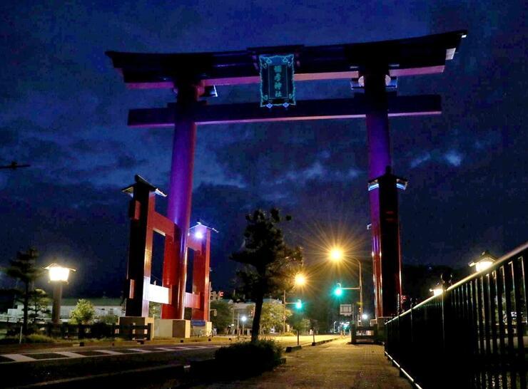 深紅の大鳥居が青みを帯びた医療関係者支援のライトアップ=1日、弥彦村