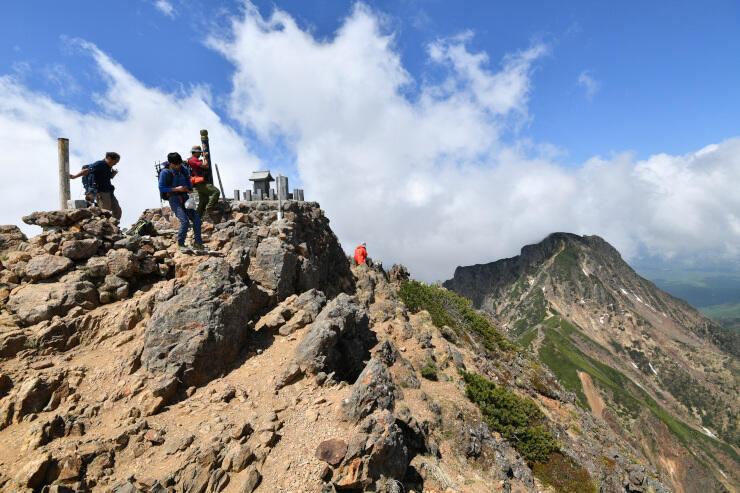 登山者がまばらな八ケ岳連峰の赤岳山頂。右奥は雲の切れ間から姿を見せた阿弥陀岳=7日午前10時27分