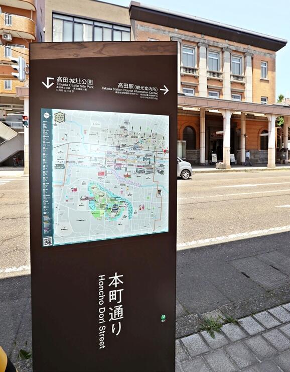 高田まちかど交流館の向かいに設置された案内看板。形状や色は雁木をイメージしている=9日、上越市本町3