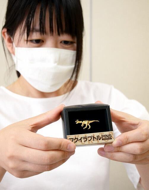 6月15日から市内4カ所で販売されるフクイラプトルのピンバッジ=福井県勝山市の勝山商工会館