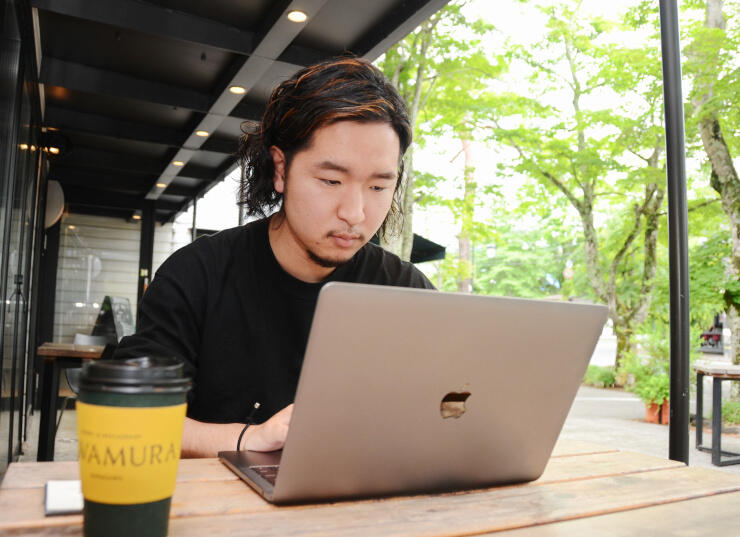軽井沢町内のカフェで動画の編集をする沢崎さん
