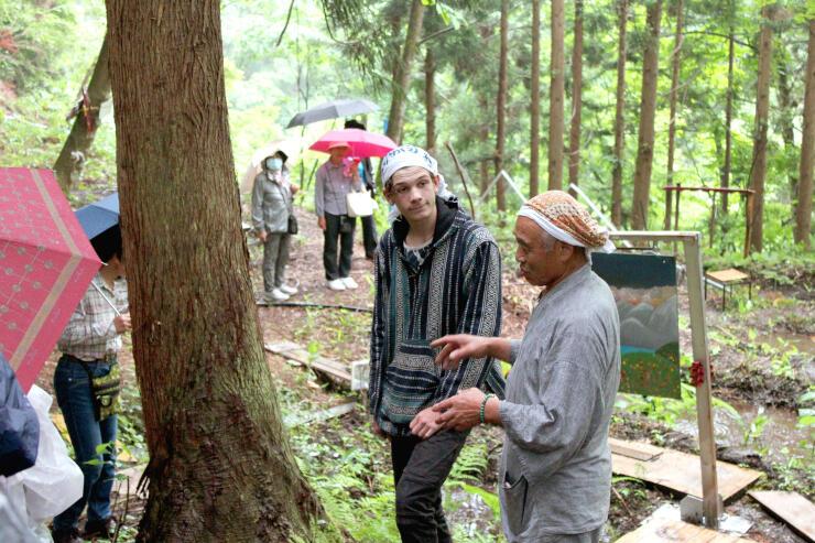 ザンダル・ボージュさん(中央)に会場を説明する佐藤賢太郎さん(右)=阿賀町