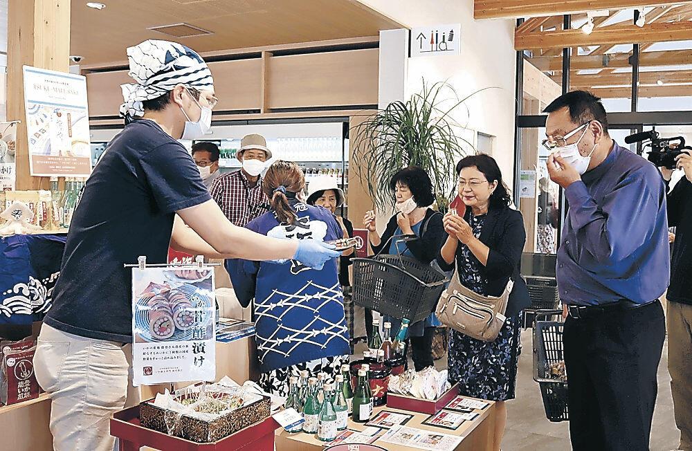 イカの甘酢漬けを試食する客=能登町のイカの駅つくモール