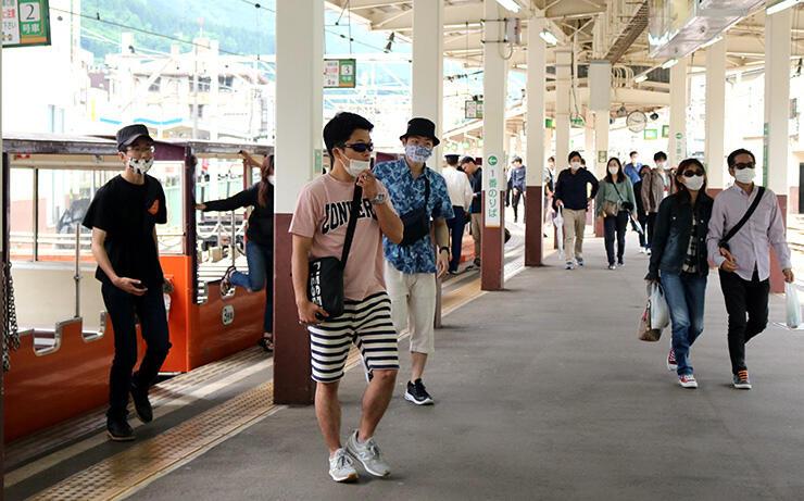 トロッコ電車の旅を終えて降車する乗客=黒部峡谷鉄道宇奈月駅