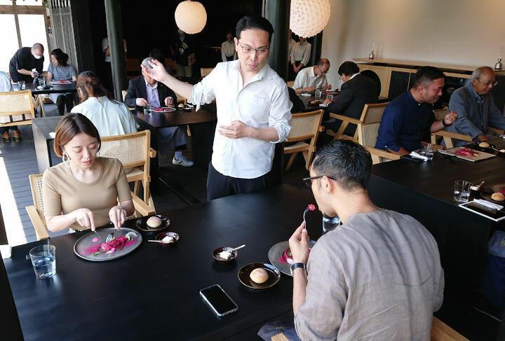 地元食材を使ったレストランのお披露目会でメニューを解説する岡部さん(中央)