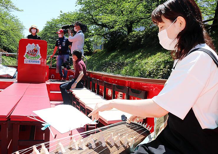 高崎さん(手前)の箏演奏で操船する中村さん(奥)