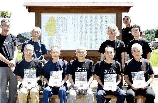 完成した解説案内板を前に記念冊子を手にする「越前・西尾友好の会」メンバー=福井県越前町天宝