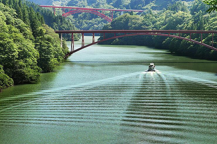 川面にしま模様の航跡を描きながら庄川峡を進む遊覧船=南砺市利賀村下原