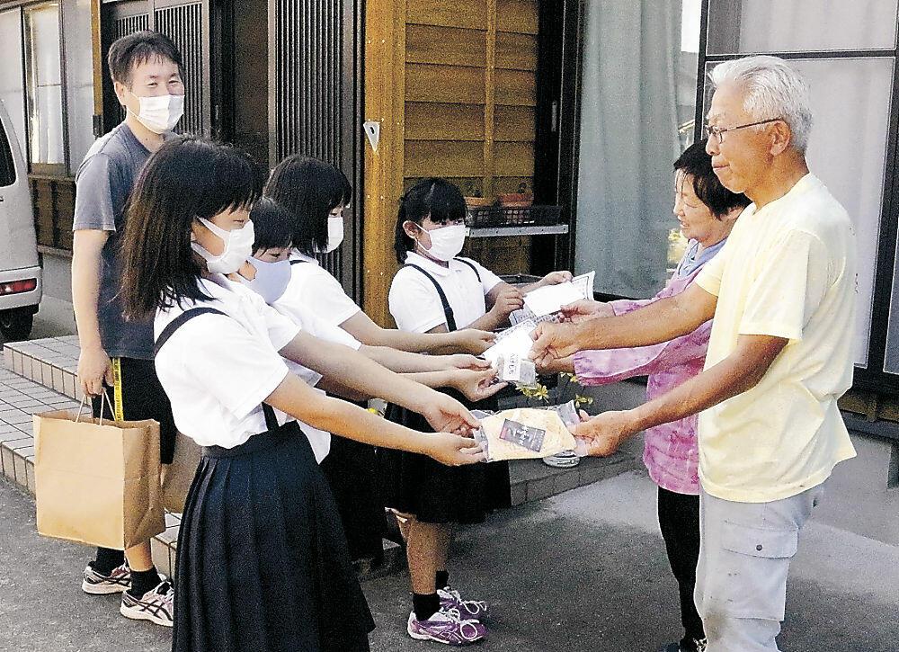 オンノキバの風習を伝えるため住民にかき餅を配る児童=珠洲市上戸町