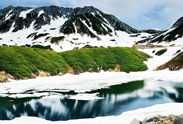 くっきりと見えた雄山(中央奥)が雪解けの進むみくりが池に映る=立山・室堂平