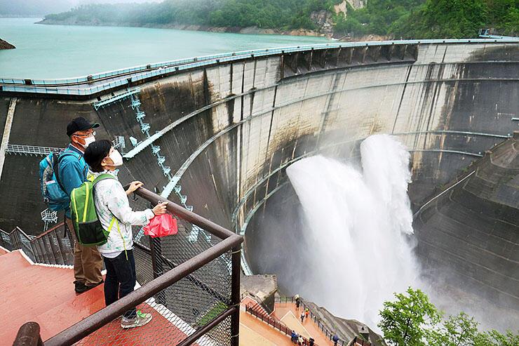 毎秒15トンの水が流れ落ちる大迫力の光景を楽しむ観光客=黒部ダム